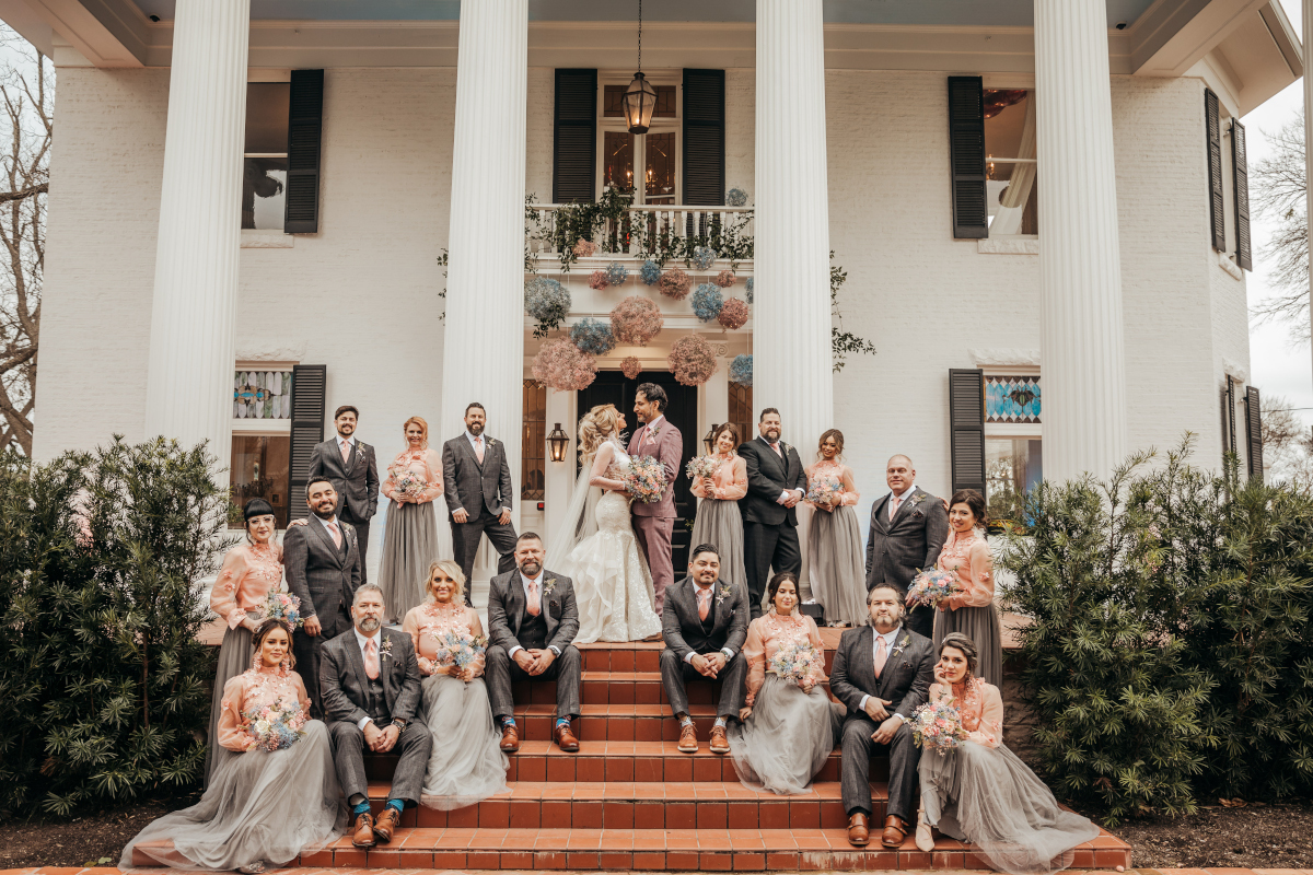 bride and groom with wedding party in front of woodbine mansion